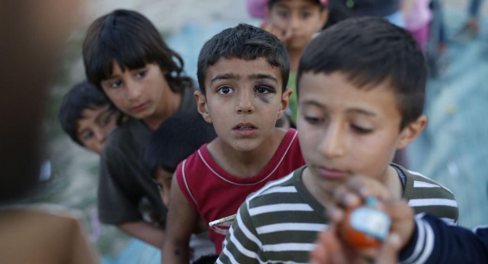Crianças na fila para receber brinquedos no campo de refugiados na Grécia