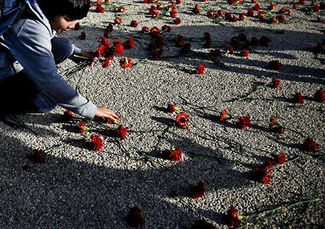 A criança apanha cravos, símbolo da Revolução portuguesa, em Lisboa, Portugal, 25 de abril de 2014