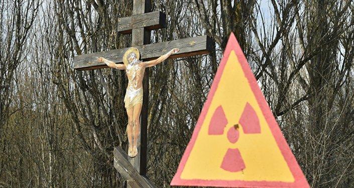 A placa indica perigo radioativo ao lado de cricifixo perto da usina nuclear de Chernobyl