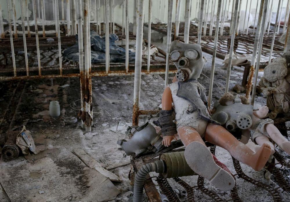 Boneco com máscara de gás no jardim de infância abandonado na zona de alienação de Chernobyl