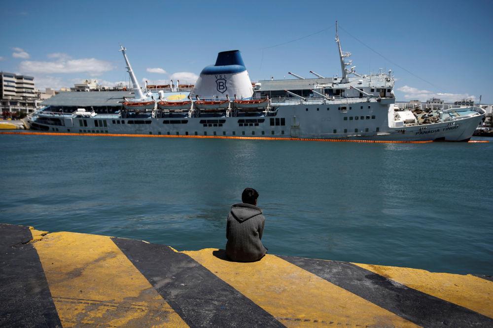 Um migrante olha para a balsa de passageiros inclinada Panagia Tinou que foi desmantelada no porto de Pireu, perto de Atenas, Grécia, 26 de abril de 2016