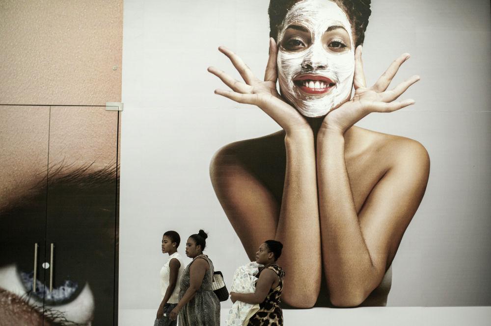 As pessoas passaram diante de um quadro publicitário do maior centro comercial na África do Sul