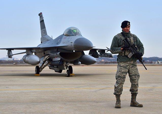 Soldado estadunidense em frente do caça F-16