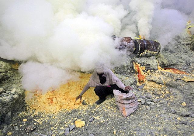 Homem coleta enxofre da cratera do vulcão Ijen, Indonésia