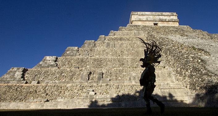 Um homem vestindo hábito maia passa na frente da pirâmide Kukulcan, no parque arqueológico Chichen Itzá, em 20 de dezembro de 2012