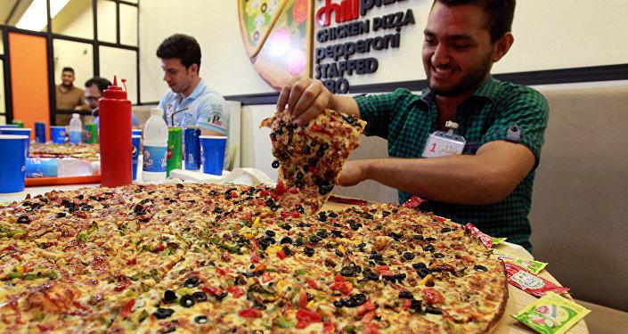 Homem iraquiano participa da competição quem come mais pizza em Bagdá, Iraque, 31 de outubro de 2015