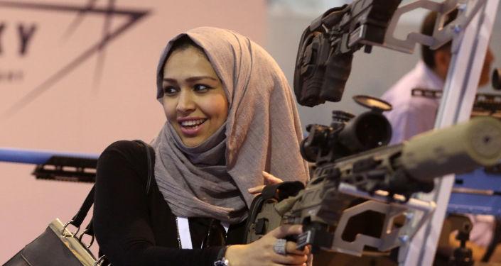 Foto de arquivo. Uma mulher jordana olha para uma arma na exibição militar SOFEX.