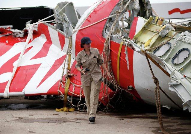 Investigadora analisa parte da cauda do AirAsia QZ8501