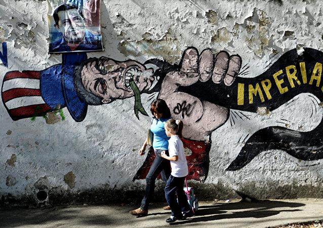 Uma mulher anda com uma menina em frente do grafite do Uncle Sam em Caracas