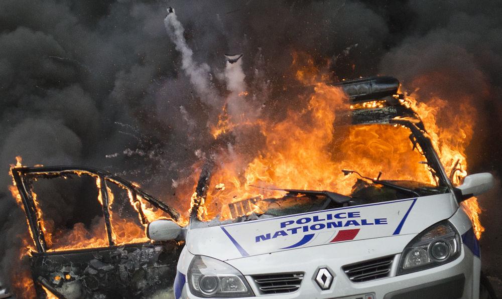 Um carro da polícia arde durante os confrontos em Paris