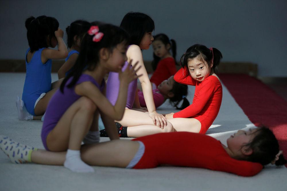 Meninas fazem exercício durante aula da ginástica na escola de esportes em Xangai, China