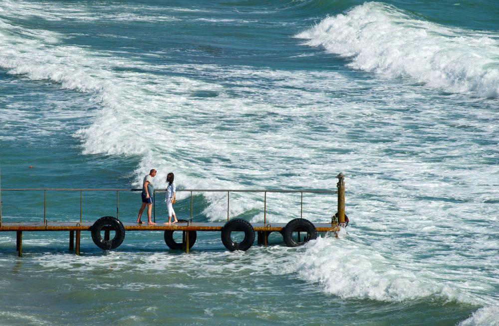 Turistas passeiam entre as águas do mar Negro na Crimeia, em 15 de maio