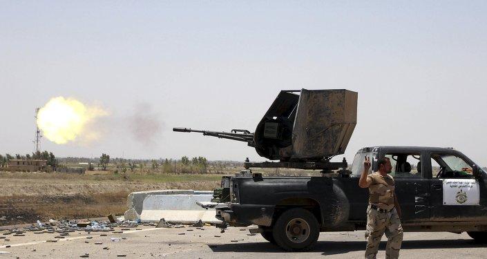 Um lutador xiita abre fogo em direção a militantes do Estado Islâmico, na cidade de Saqlawiyah, perto de Faluja, Iraque 04 de agosto de 2015