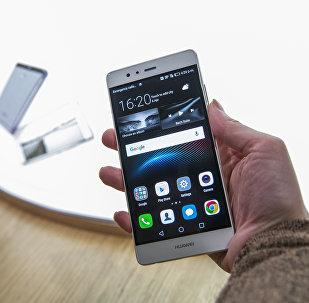 Mulher mostra um novo smartphone feito pela manufaturadora chinesa Huawei, Londres, Reino Unido, abril de 2016