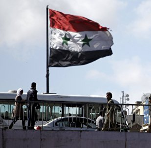People walk near a Syrian national flag at the President bridge in Damascus