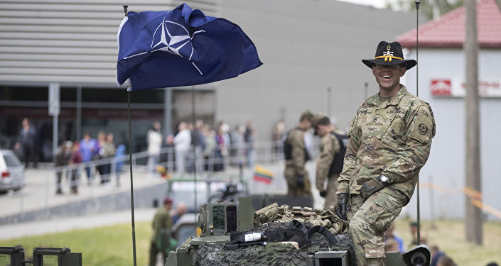 """Um membro do Exército dos EUA posa num carro blindado durante os exercícios militares """"Dragoon Ride II"""" perto de Vilnius, Lituânia, junho de 2016"""