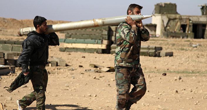 Soldados do exército sírio carregam um missil a ser disparado contra as posições do Daesh em Raqqa