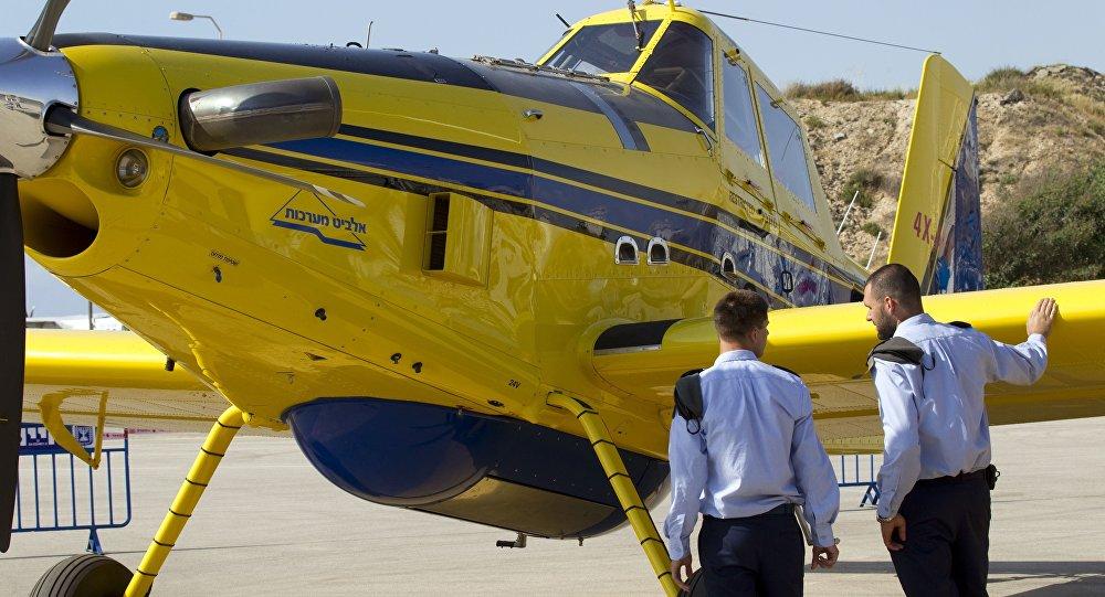 Pilotos israelenses ao lado de um avião do corpo de bombeiros
