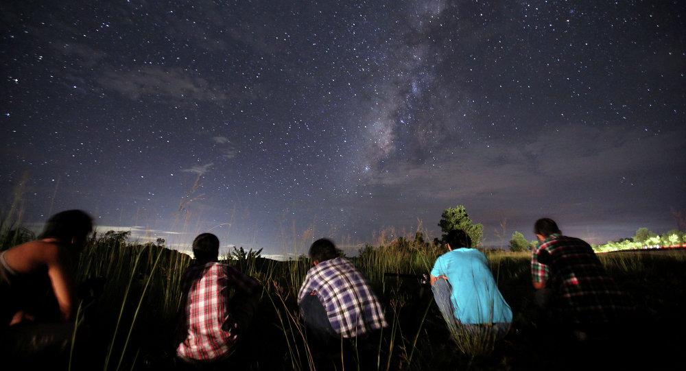 pessoas observam o céu escuro