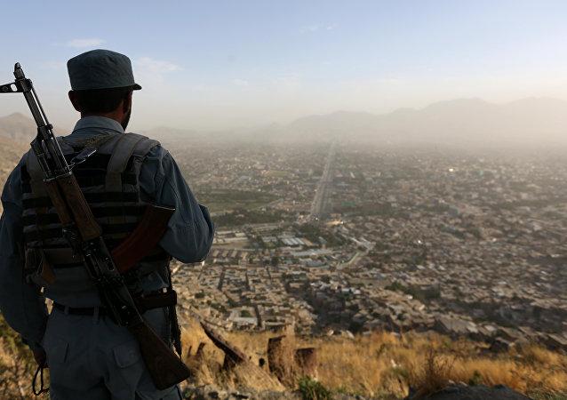 Nesta foto de 21 de junho de 2016, um policial do Afeganistão olha a cidade de Cabul, capital do país, de uma elevação