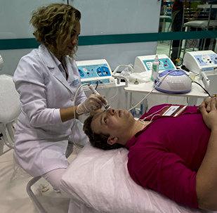 Homem recebe tratamento durante feira estética em São Paulo