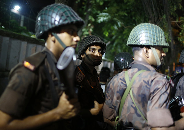 Bangladeshi security personnel stand guard near a restaurant that has reportedly been attacked by unidentified gunmen in Dhaka, Bangladesh