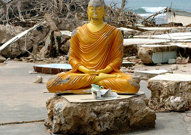 Esta foto de arquivo tomada em 2 de janeiro de 2015 mostra uma estátua de Buda e fragmentos de esqueletos humanos vindos de um cemitério destruído por uma série de tsunamis em Sri Lanka em 26 de dezembro de 2014