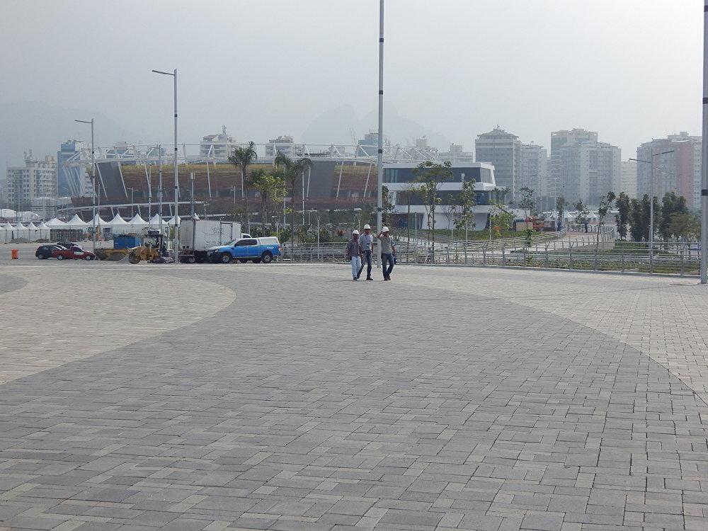 Operários do Parque Olímpico com o Velódromo ao fundo
