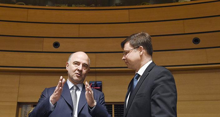 Pierre Moscovici e Valdis Dombrovskis durante um evento em 17 de junho de 2016