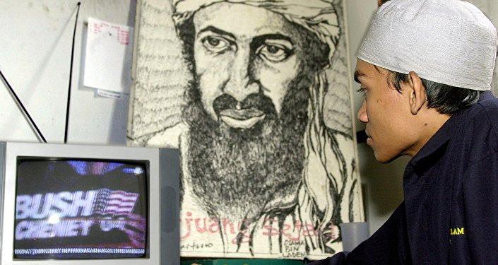 Um jovem muçulmano indonésio assiste a uma cobertura televisiva das eleições nos EUA na frente do retrato de Osama bin Laden, 03 de novembro de 2004