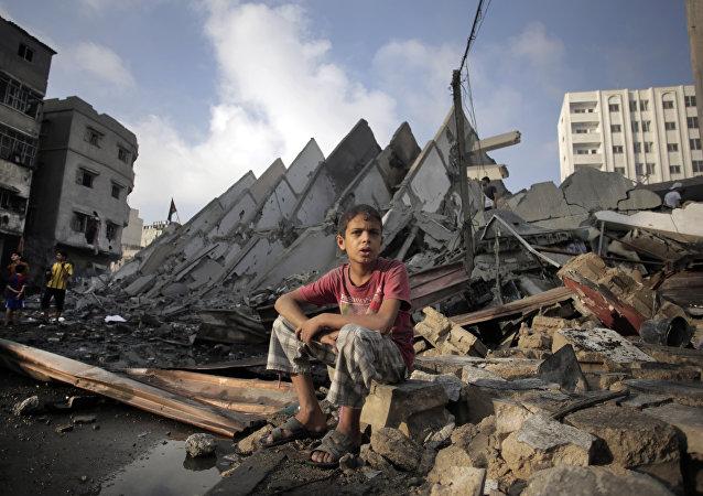 Menino palestiniano sentado sobre ruínas depois de bombardeio da Faixa de Gaza por Israel, agosto de 2014