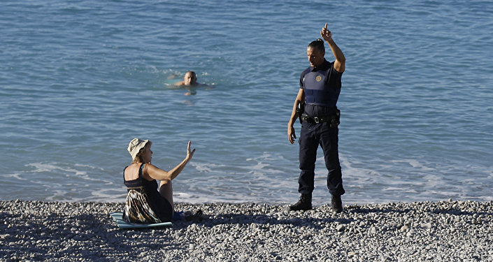 Um policial pede a nadadores para deixarem a praia