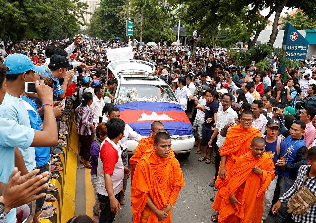 Um carro fúnebre carregando o corpo de Kem Ley, uma figura anti-governo e o cabeça de um grupo Khmer para Khmer, é cercado por seus partidários no caminho de um pagode para uma cerimônia budista depois que foi disparado morto em Phnom Penh. 10, julho, 2016.