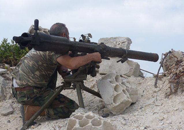 Um soldado do exército sírio aguarda com morteiro o inimigo