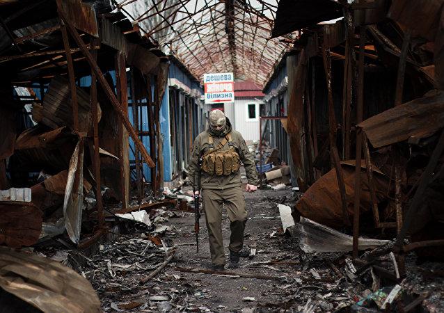 Combatente da República Popular de Donetsk em um mercado destruído no leste ucraniano