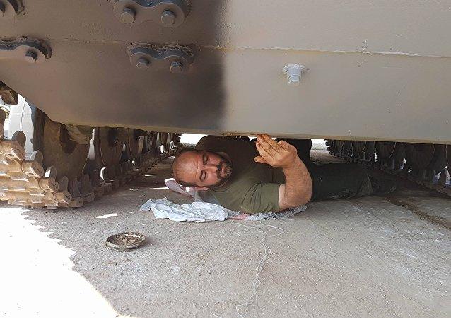 Um militar iraniano examina um tanque antes dos Jogos do Exército na Rússia