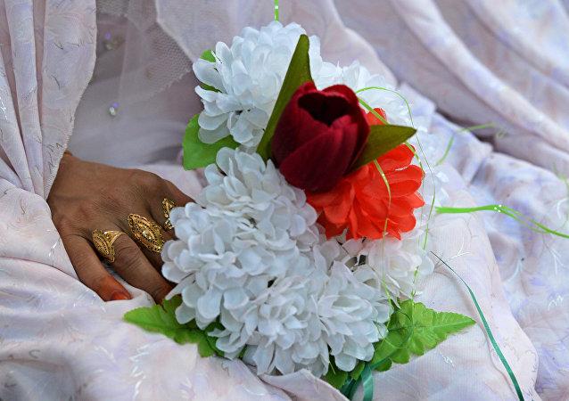 A noiva afegã com um ramalhete de flores durante uma cerimônia de casamento em massa na qual uma centena de casais se casaram na periferia de Cabul