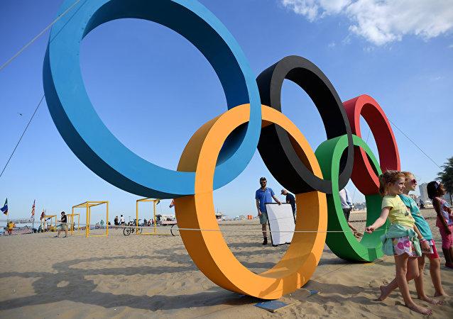 As crianças ao lado dos anéis olímpicos na praia de Copacabana, no Rio de Janeiro, no dia 01 de agosto de 2016 antes dos Jogos Olímpicos no Rio 2016