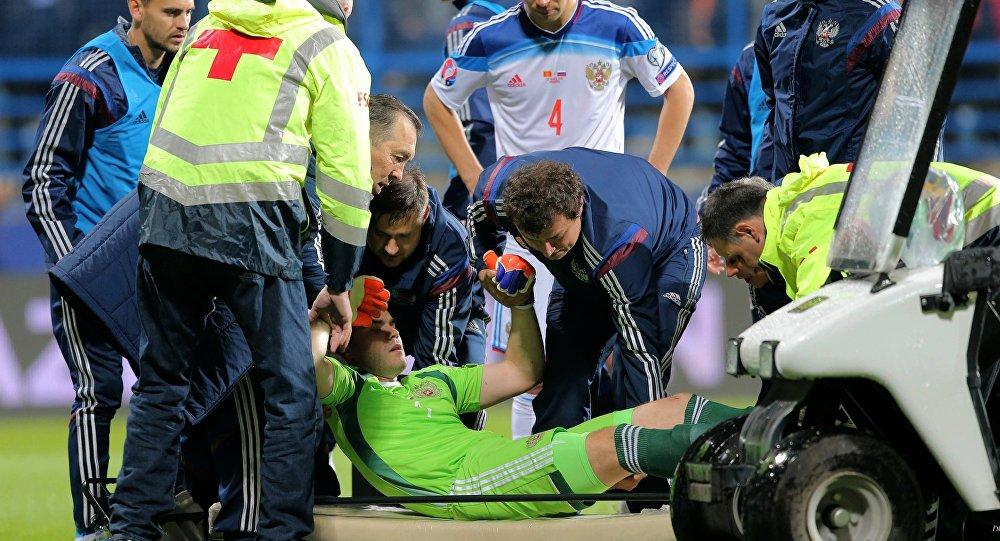 Goleiro Igor Akinfeev recebe atendimento médico em partida contra a seleção de Montenegro