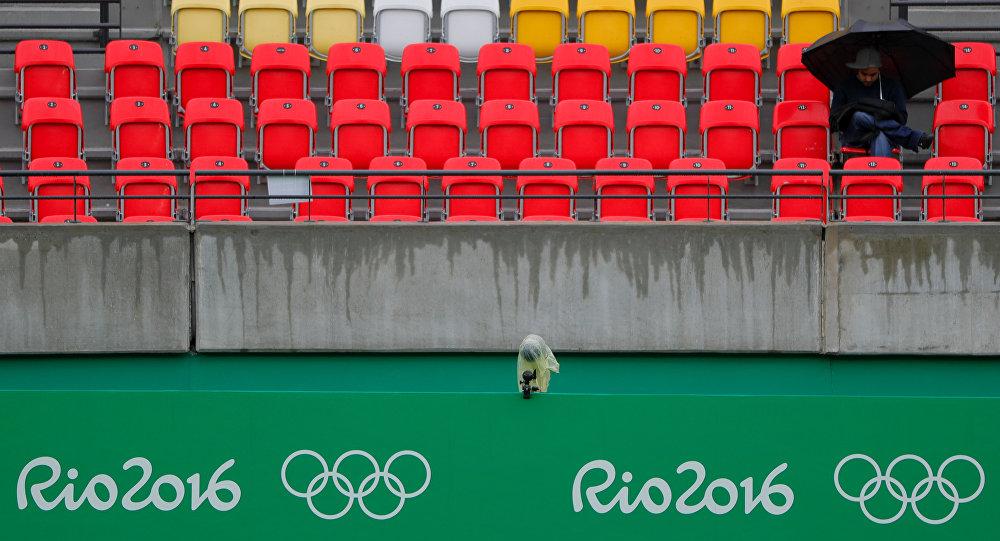 Um espectador senta-se sob o guarda-chuva na tribuna de uma quadra de tênis; partidas são atrasadas devido à chuva no Rio
