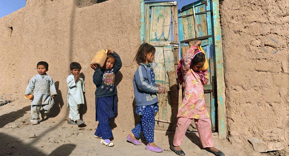 Crianças desalojadas passeiam no campo de refugiados no oeste de Cabul, Afeganistão, março de 2012