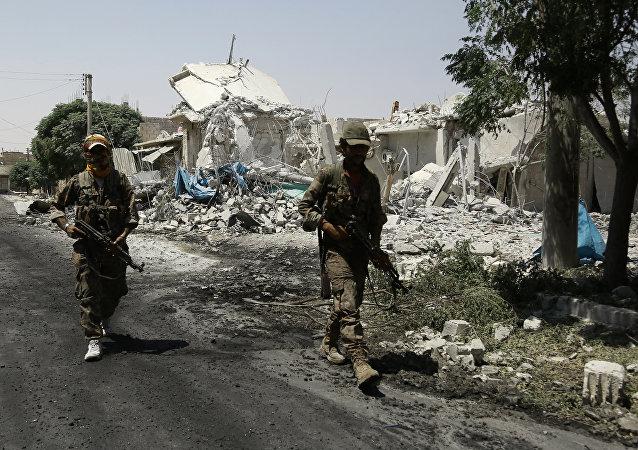 Combatentes das Forças Democráticas da Síria passam edifícios destruídas na cidade de Manbij, 7 de agosto de 2016