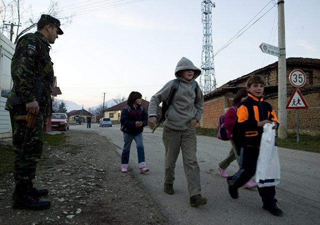 Um soldado romeno da força pacificadora da ONU guarda a passagem de crianças sérvias que vão à escola no enclave sérvio no Kosovo de Gorazdevac, em 2007 (foto de arquivo)