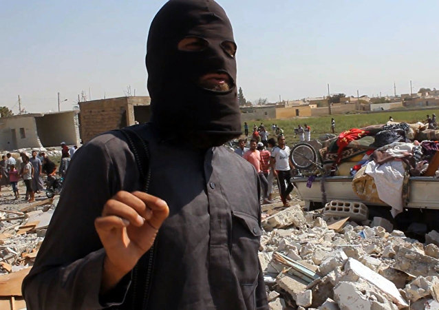 Um militante do Estado Islâmico caminha sobre escombros na Síria.