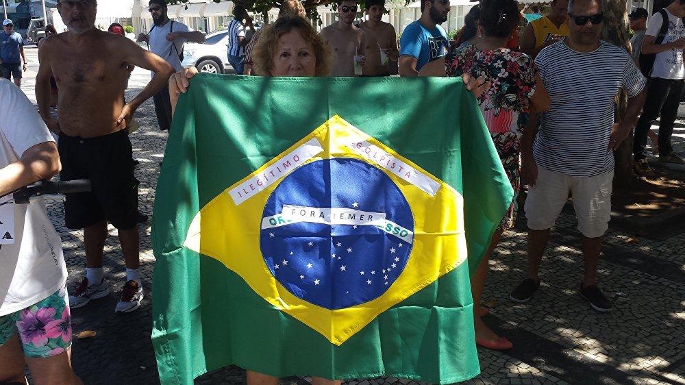 Senhora mostra bandeira do Brasil com mensagens para o novo presidente