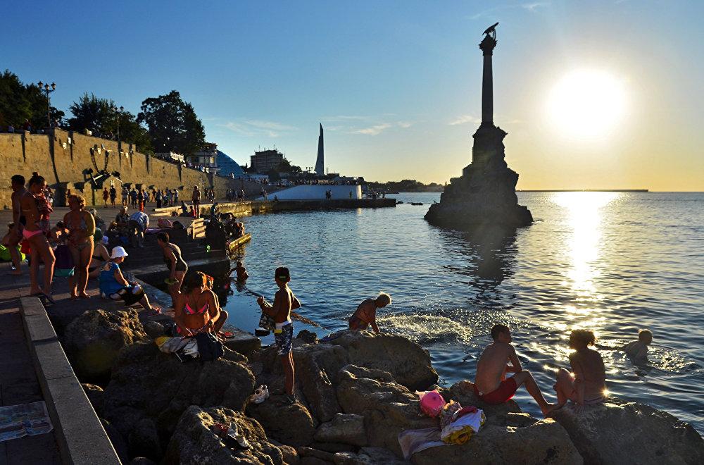 Turistas e moradores locais se banham perto do monumento aos navios afundados em Sevastopol