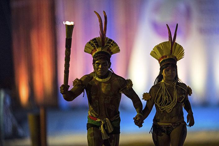 Um homem e uma mulher indígenas passam com a tocha de inauguração dos Jogos Mundiais Indígenas em Palmas, Tocantins, em 23 de outubro de 2015