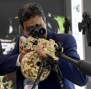 Visitante do fórum EXÉRCITO 2016 examina uma metralhadora ligeira RPK-16 da empresa Kalashnikov