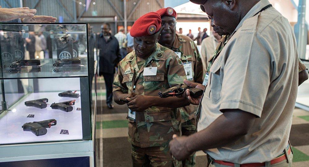 Delegados africanos examinando armas apresentadas na exposição Africa Aerospace and Defence 2016 em Johannesburgo