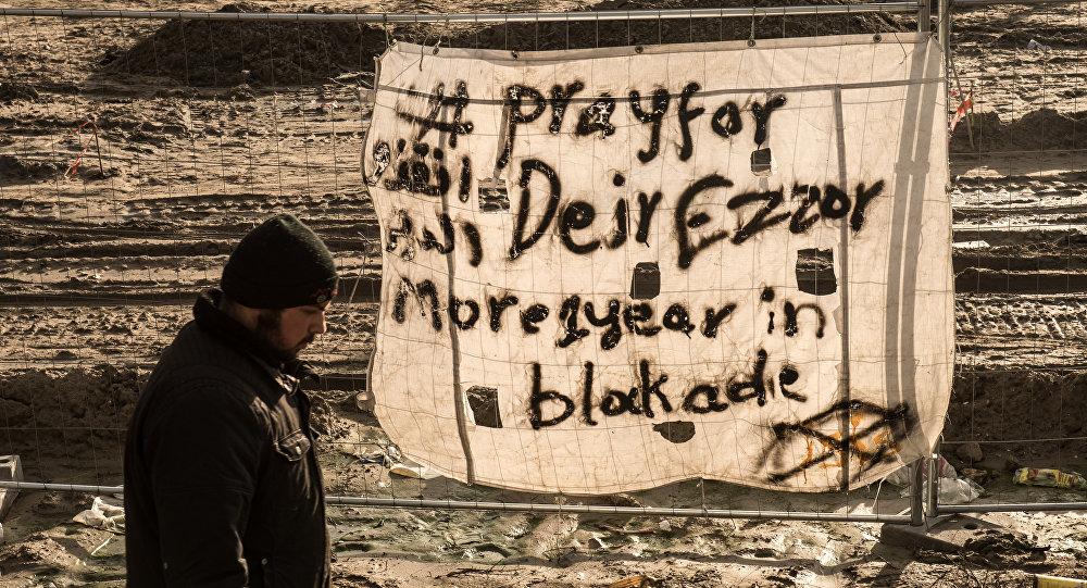 Uma pessoa passa em Calais, França, perto de um cartaz dizendo, em inglês: Ore por Deir ez-Zor, mais de 1 ano sob sítio
